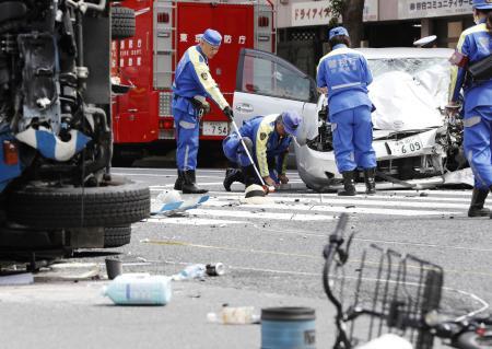 交通事故の現場を調べる警察官=4月、東京都豊島区